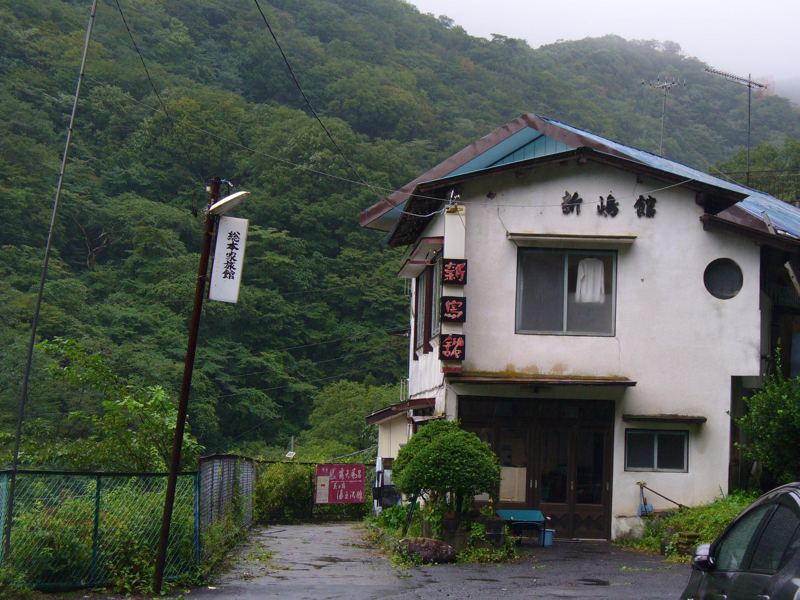 現在は廃業されている? 新嶋館。左下に、湯之沢館の案内看板が……。