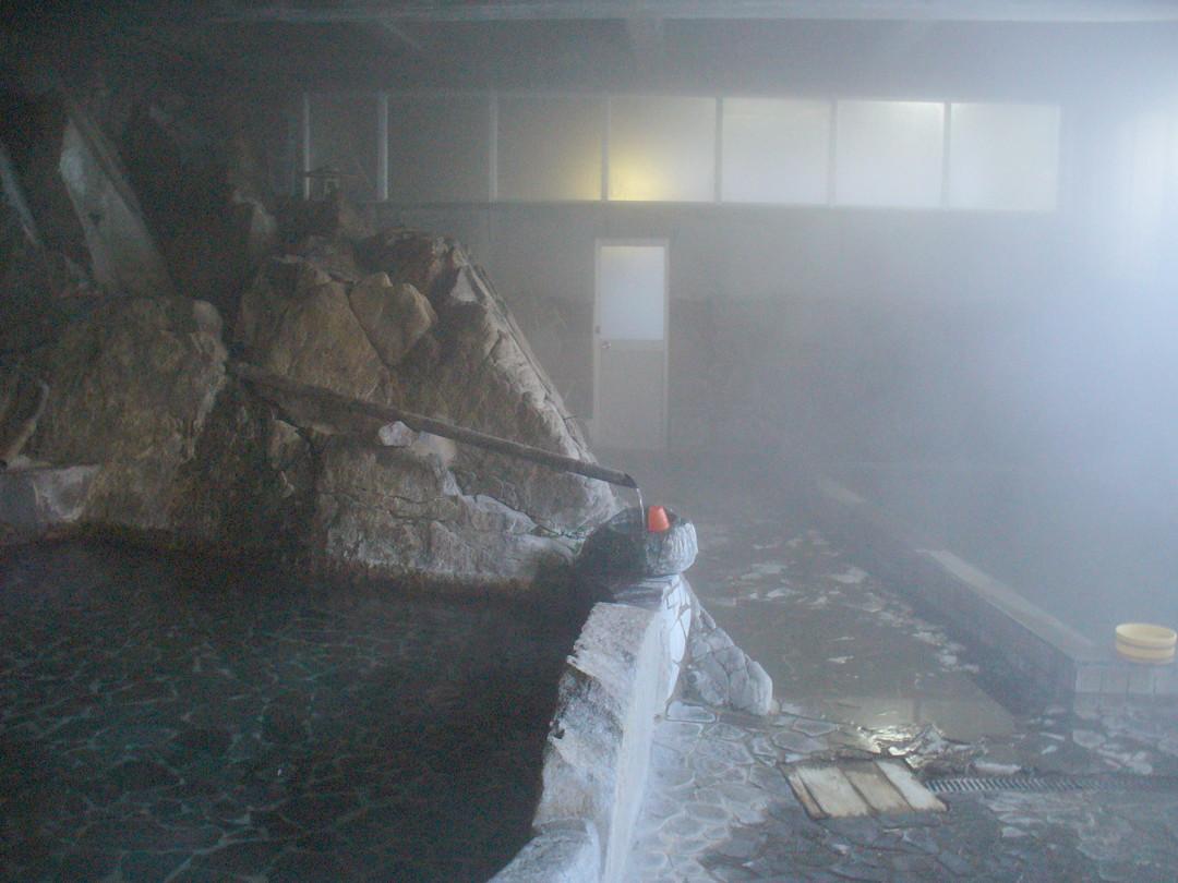 大きなほうの内湯。左の広い岩風呂が源泉、右の浴槽が加温浴槽。